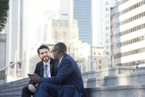 Two businessmen sitting on stairs talking and sharing tablet in city — Stock Photo