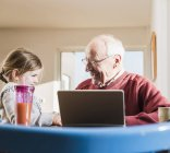Grandfather and granddaughter using laptop together — Stock Photo