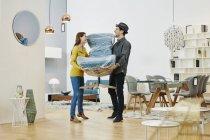 Ritratto di coppia che tiene pranzo sedia in negozio di mobili — Foto stock