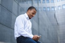 Businessman using smartphone in front office building — Stock Photo
