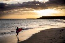 Отдаленное представление о подростка мальчика, перевозящих серфинга на пляже на красивый закат — стоковое фото