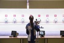 Femme devant les cibles dans un stand de tir — Photo de stock
