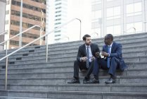 Two businessmen sitting on stairs and talking — Stock Photo