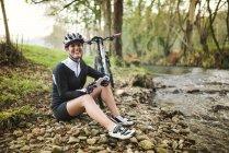 Mujer con bicicleta de montaña de descanso en la naturaleza - foto de stock