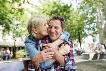 Heureux couple âgé mignon assis ensemble sur le banc et câlin au parc — Photo de stock