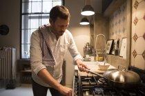 Концентрированные человек, приготовление пищи на кухне дома — стоковое фото