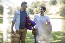 Cape Town, South Africa,Two male friends with picnic baskets walking on garden walk — Stock Photo