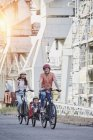 Portrait of family cycling with daughter in trailer — Stock Photo
