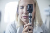 Female pedeatrician using a otoscope — Stock Photo