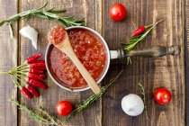 Saucepan of homemade tomato sauce and ingredients on wood — Stock Photo