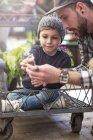 Niño sentado en el carro en el centro de jardinería, padre mostrando algo - foto de stock