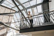 Бизнесмен, стоящий на верхнем этаже — стоковое фото