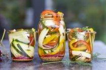 Verduras en vinagre y hierbas en frasco de conservación en superficie gris - foto de stock