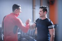 Two young men shaking hands in gym — Stock Photo