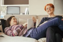 Mother and adult daughter with digital tablet on couch — Stock Photo