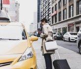 Жінка, стоячи на таксі в Манхеттен, Нью-Йорк, США — стокове фото