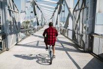 Man riding bicycle on bridge — Stock Photo