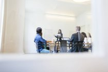 Business people having a team meeting behind glass doors — Stock Photo