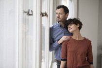Couple looking through window at home — Stock Photo