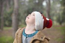 Ragazzo che porta cappello lanoso che osserva in su nella foresta — Foto stock