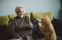 Felice donna anziana giocando con gattino zenzero a casa — Foto stock