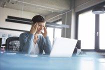 Empresaria con la cabeza en las manos usando portátil en la oficina - foto de stock