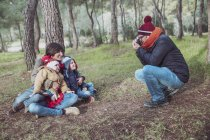 Father taking a picture of his family in forest — Stock Photo