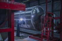 Man welding large steel tank in factory — Stock Photo
