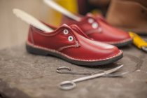 Sapatos vermelhos inacabados na oficina do sapateiro — Fotografia de Stock