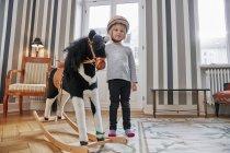 Jeune fille debout à côté du cheval à bascule — Photo de stock