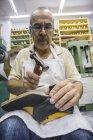 Шумейкер, работа с молотка на обуви в своей мастерской — стоковое фото