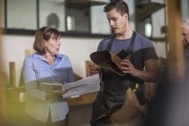 Woman with tablet talking to shoemaker in workshop — Stock Photo