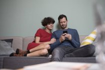Couple sitting together on couch and sharing cell phone — Stock Photo