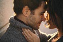 Nahaufnahme eines liebevollen Paares, das Gesicht an Gesicht im Sonnenlicht steht — Stockfoto