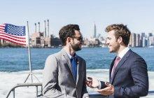Due uomini d'affari che parlano in traghetto sull'East River, New York, USA — Foto stock