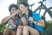 Jovem casal de mountain bike na natureza, fazendo uma pausa debaixo da árvore — Fotografia de Stock