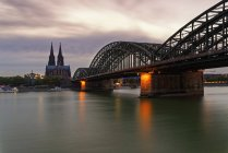 Germany, Cologne, view to Cologne Cathedral with Hohenzollern Bridge in the foreground at evening twilight — Stock Photo