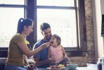 Madre e padre che alimenta la piccola figlia in cucina — Foto stock