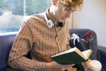 Jovem com café para ir sentado em um trem lendo um livro — Fotografia de Stock