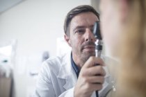 Médecin utilisant un otoscope — Photo de stock