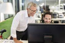 Двоє чоловіків усміхнений в офісі, дивлячись на монітор комп'ютера — стокове фото