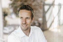 Ritratto di uomo d'affari sorridente che distoglie lo sguardo in ufficio — Foto stock