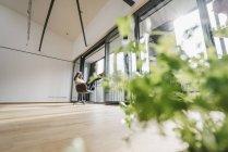 Mulher sentada na cadeira na janela na sala vazia com planta — Fotografia de Stock