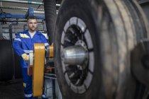 Male repairman tuning tire on machine — Stock Photo