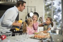 Father with little girls cooking together in kitchen — Stock Photo