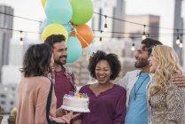 Друзі представлення торт до дня народження для молодої жінки африканських на даху партії — стокове фото