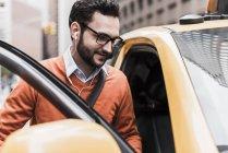Uomo d'affari entrando taxi giallo, New York City, Stati Uniti — Foto stock