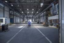 Worker on bicycle in warehouse — Stock Photo