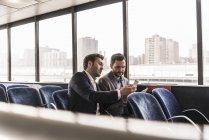 Zwei Geschäftsleute mit Mobiltelefonen im Gespräch auf dem Passagierdeck einer Fähre — Stockfoto