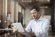 Бизнесмен с помощью планшета в офисе — стоковое фото